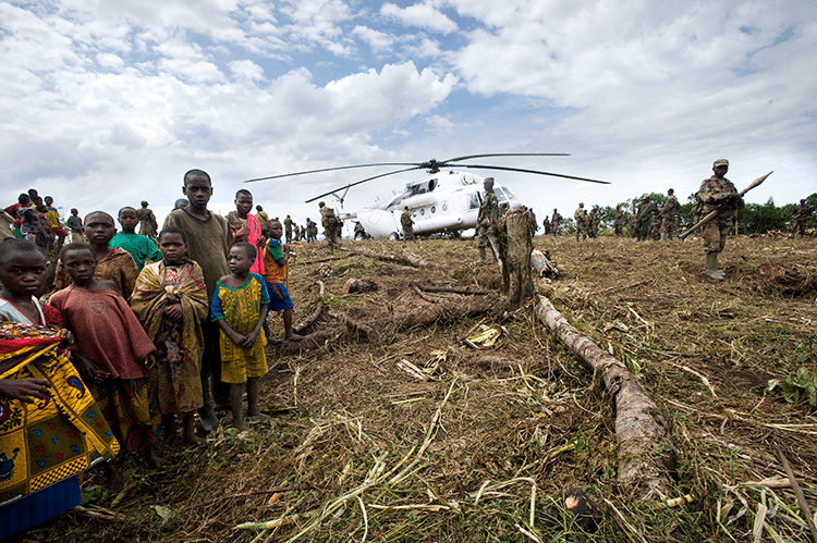 Villagers watch as a helicopter lands at an army base of the Congolese forces near Kashunga