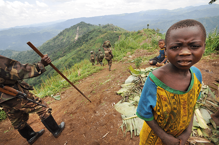 Rwandan Defense Force (RDF) troops walk thru this mountain top village in the remote reaches of Walikali district .