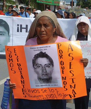 "Delfina de la Cruz, mother of missing student Adán Abraján de la Cruz marches holding a sign that says: ""We are the students. Why do they murder us?"" Photo: Témoris Grecko"