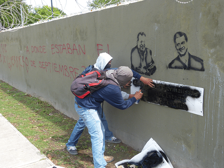 """Portraits of President Peña Nieto and then-governor of Guerrero Ángel Aguirre. The caption reads: """"Murderers of students. Crime of the state. Cynicism of the state."""" Photo: Témoris Grecko"""