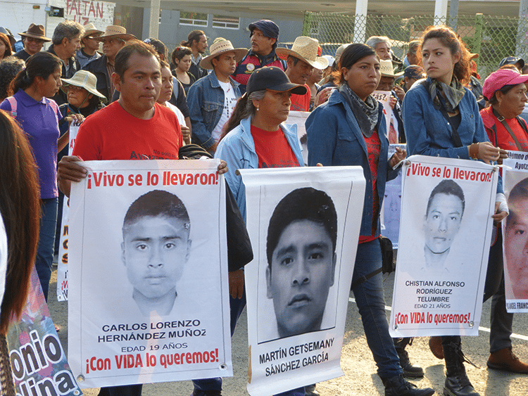 "Maximino Hernández (in red), father of Carlos Lorenzo, holds a sign that reads: ""Taken alive! We want him back alive!"" Photo: Témoris Grecko"