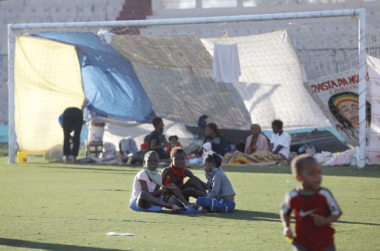 Children sit on the pitch and talk in the Sylvio Cator stadium which was used as a temporary home for many displaced people after the earthquake. Julie Jacobson/AP/Press Association Images