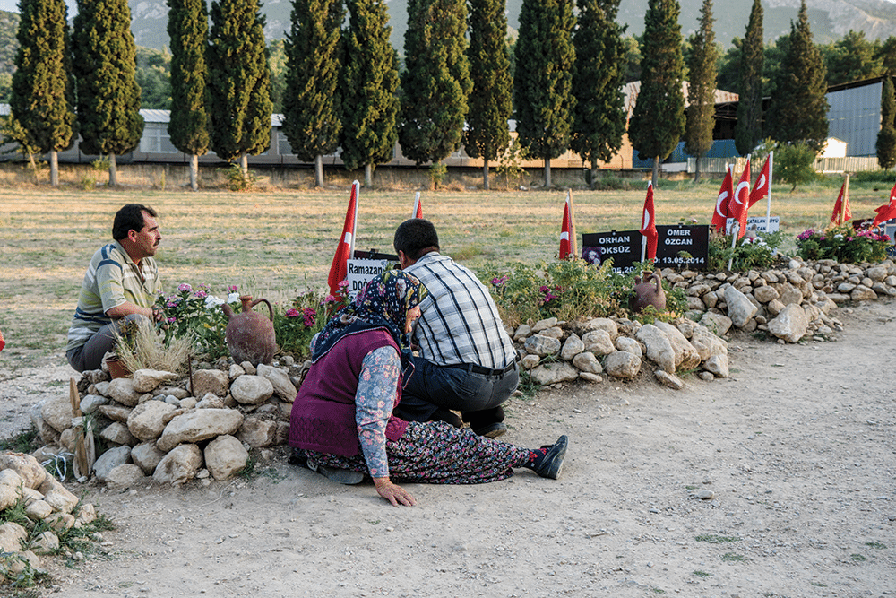 A mother with her two sons visit the grave of her third, Ramazan, who was killed in the Soma mine. Photo: Guy Martin
