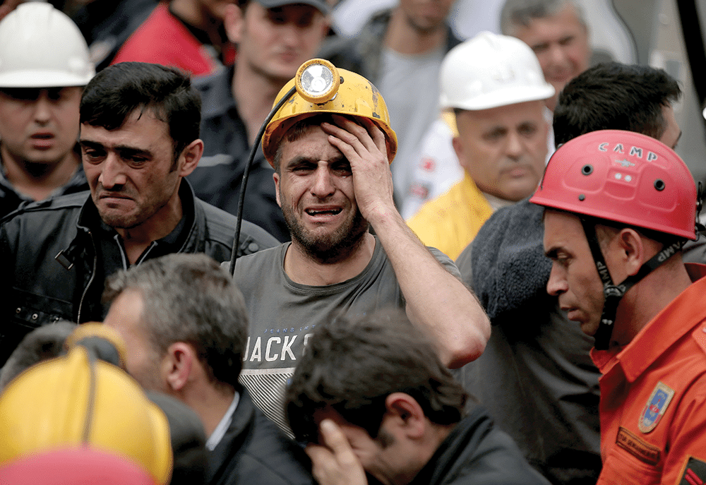 Miners watch as rescue workers carry bodies from the mine in Soma on Wednesday 14th May Photo: Emrah Gurel/AP/Press Association Images