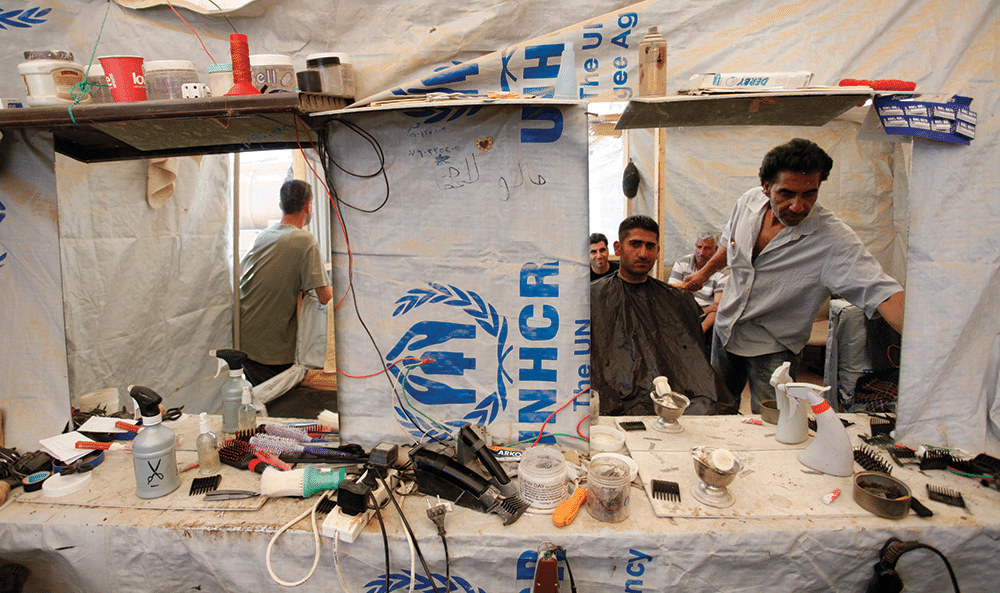 Abd al-Raouf Abo Majd, 45, right, known as 'the Zaatari barber', cuts a Syrian refugee's hair in his UNHCR tent barbershop, at Zaatari refugee camp on 25th April 2013. Photo: Mohammad Hannon/AP/Press Association Images