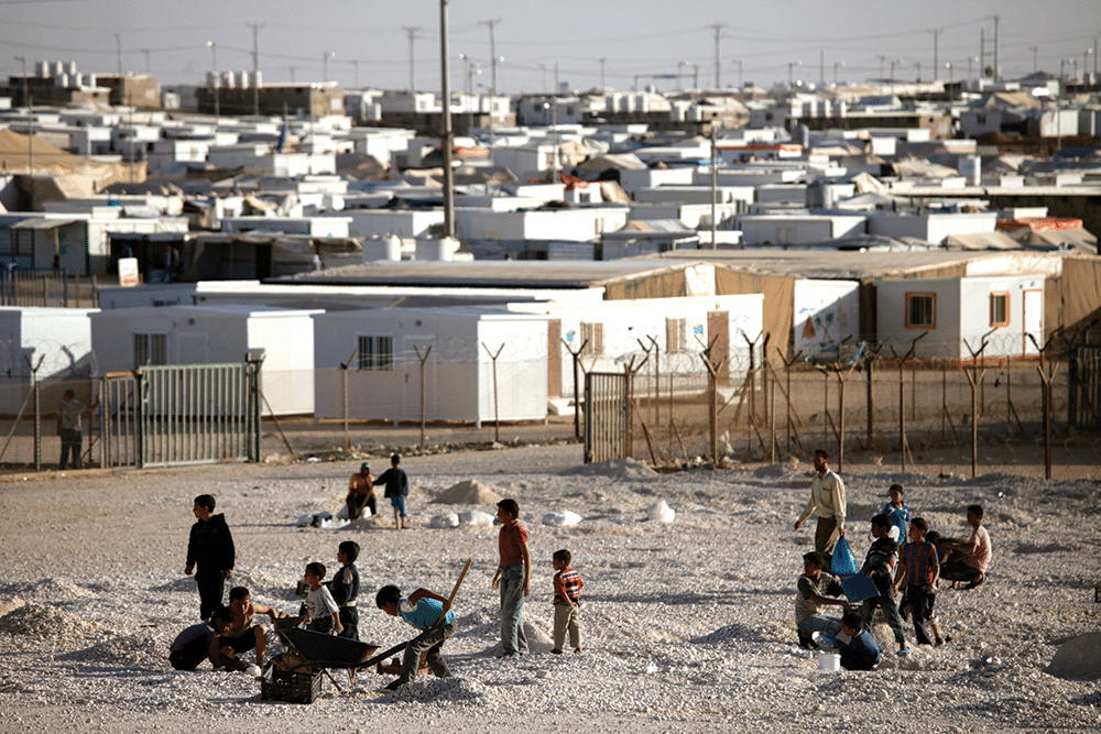 Syrian refugees work in the gravel yard, which is used to help protect their homes from rainwater. Photo: Mohammad Hannon/AP/Press Association Images