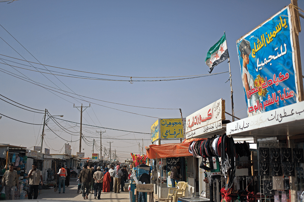 Syrian refugees and aid workers mix on a market street in Zaatari in April 2014