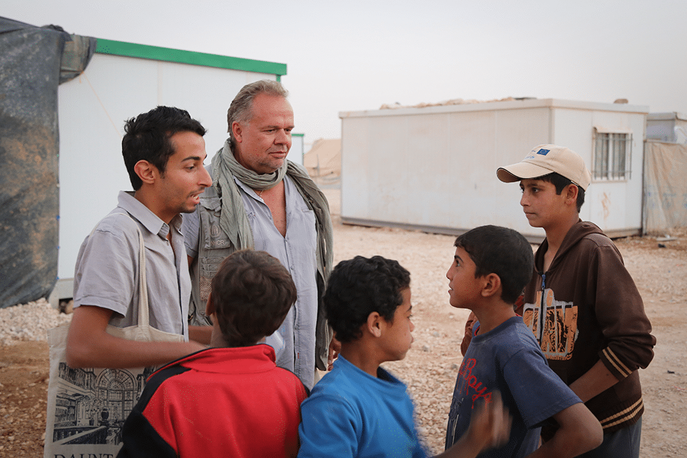 UN official Kilian Kleinschmidt and journalist Sakhr Al-Makhadhi talk to some of Zaatari's younger residents in 2013