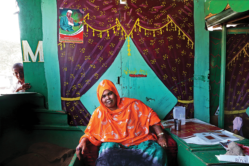 Khat queen Kaltuna Ismail Kabadhe in her outlet. Kaltuna is one of the first women to gain influence in the male-dominated world of politics, and hangs campaign posters for local candidates in her stalls