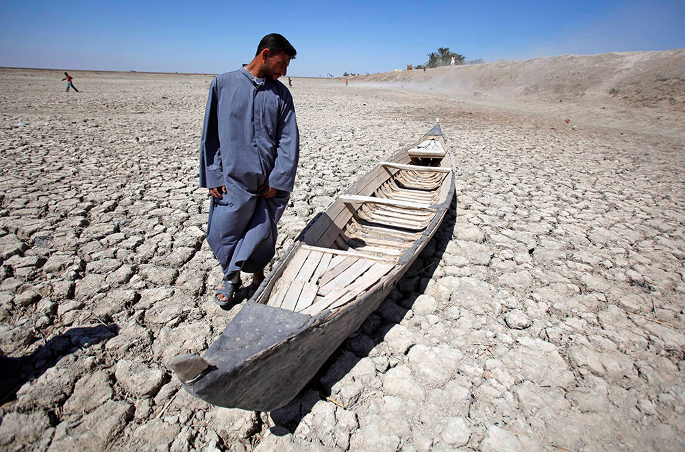 A man stands next to his boat in a dried marsh in Hor al-Hammar in southern Iraq. Photo: AP/Press Association Images/Hadi Mizban