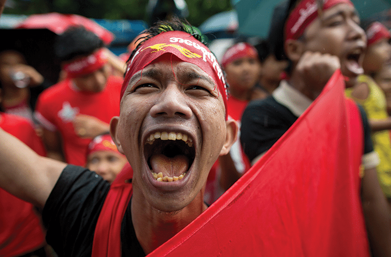 myanmar03 An NLD supporter celebrates outside the party headquarters on 9th November. The UEC didn't post the official results until 13th November, but local wins gave the party confidence early on. Photo: AP/Press Association Images/Gemunu Amarasinghe