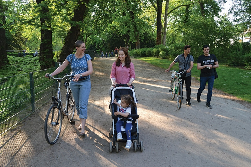 German volunteer Alexandra Einmahl and Joud Na from Aleppo, Syria, walk to a Start With a Friend group picnic in Cologne's Volksgarten on 11th May. Photo: Matthew Lee