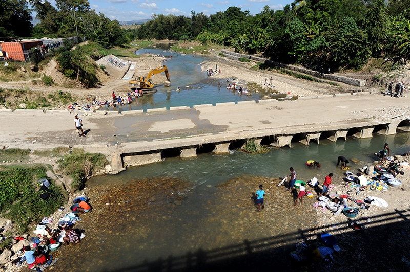People wash their clothes in a river in Mirebalais. Plans for the development of critical water and sanitation facilities haven't materialised, meaning people still rely on the same waterways that were responsible for the spread of cholera