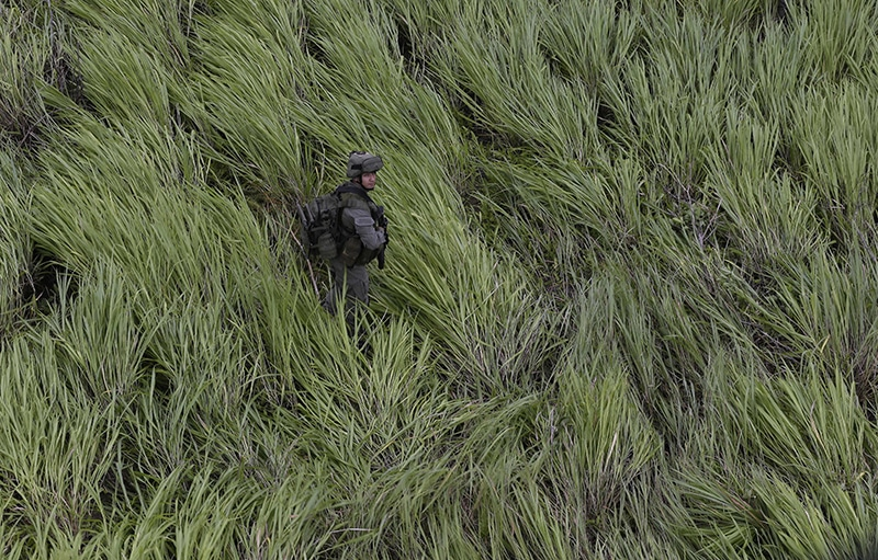 An anti-narcotics police officer stands guard at a landing zone near a cocaine lab in Calamar, Colombia in August 2016. Photo: Fernando Vergara/AP/Press Association Images