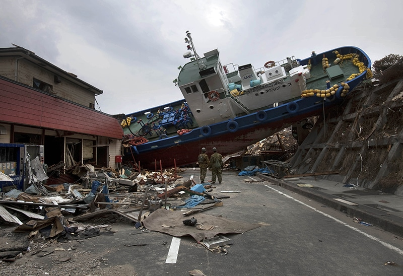 Two Japanese soldiers stop to look at a ship blocking a road they are trying to clear on 20th March 2011 after the earthquake and subsequent tsunami destroy the town of Onagawa. Photo: David Guttenfelder/AP/Press Association Images
