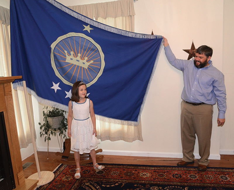 Jeremiah Heaton and his daughter Emily stand alongside their homemade blue flag. Photo: David Crigger/AP/Press Association Images