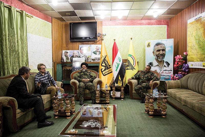 Commander Ali al-Yaseri of Saraya al-Khorasani (far right) is accompanied by deputy commander Hamid al-Jazaeiri for our interview. Pictures of Iranian generals including Hamid Taghavi (large poster on right) and Qassem Suleimani adorn the walls
