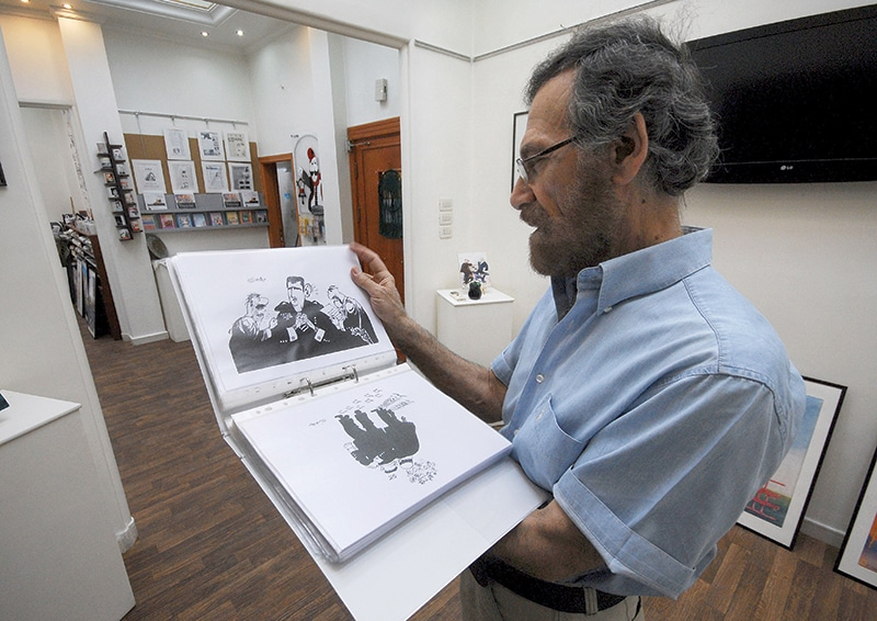 Cartoonist Ali Ferzat shows his work in August 2011, days before an attack in which his hands were broken. Photo: Muzaffar Salman/AP/Press Association Images