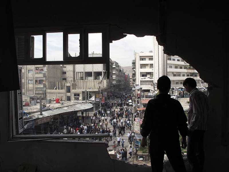 Syrian youth stand in a building damaged by tank shells in a neighborhood of Damascus, April 2012. Photo: Anonymous/AP/Press Association Images