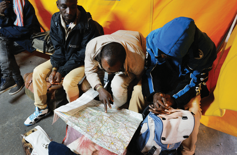 In Calais, Sudanese men study a map before boarding a bus taking them to their temporary accommodation, 25th October 2016.  Photo:  John Stillwell / PA Wire / PA Images