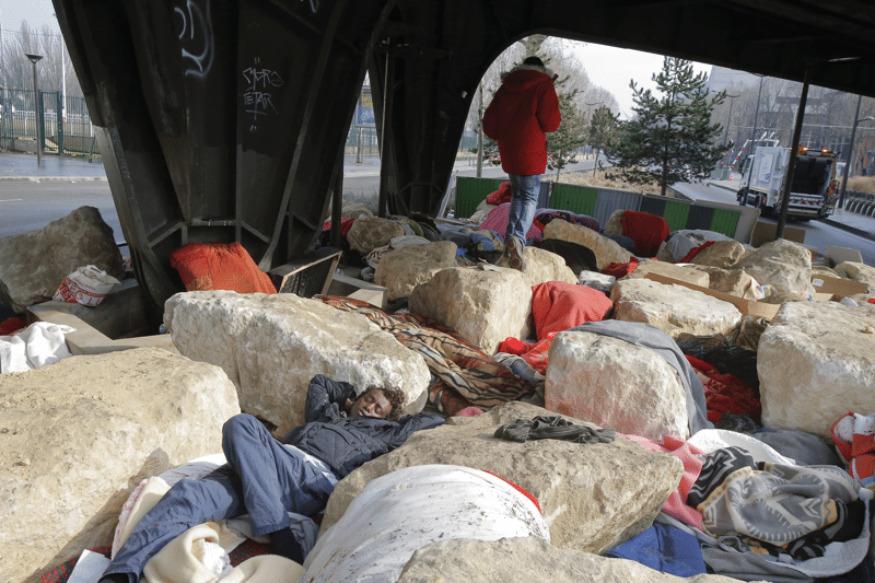 Migrants and refugees sleep in the spaces between boulders on 16th February 2017 at Porte de la Chapelle, Paris.  Photo: Michel Euler / AP / PA Images